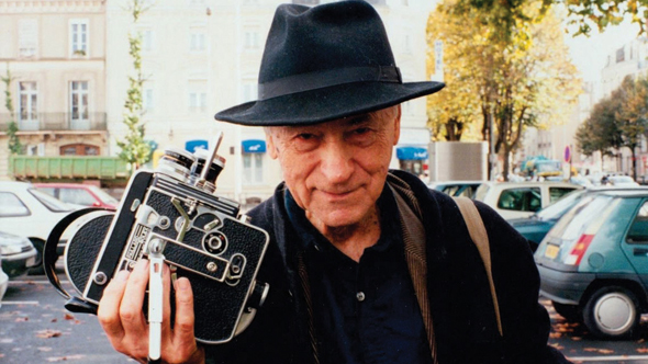 Jonas Mekas holding his 16mm Bolex camera